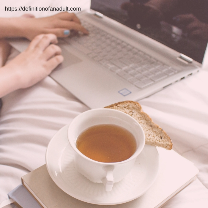 It's Difficult to Find Your First Full-Time Job – Image a laptop, hands, tea on a bed